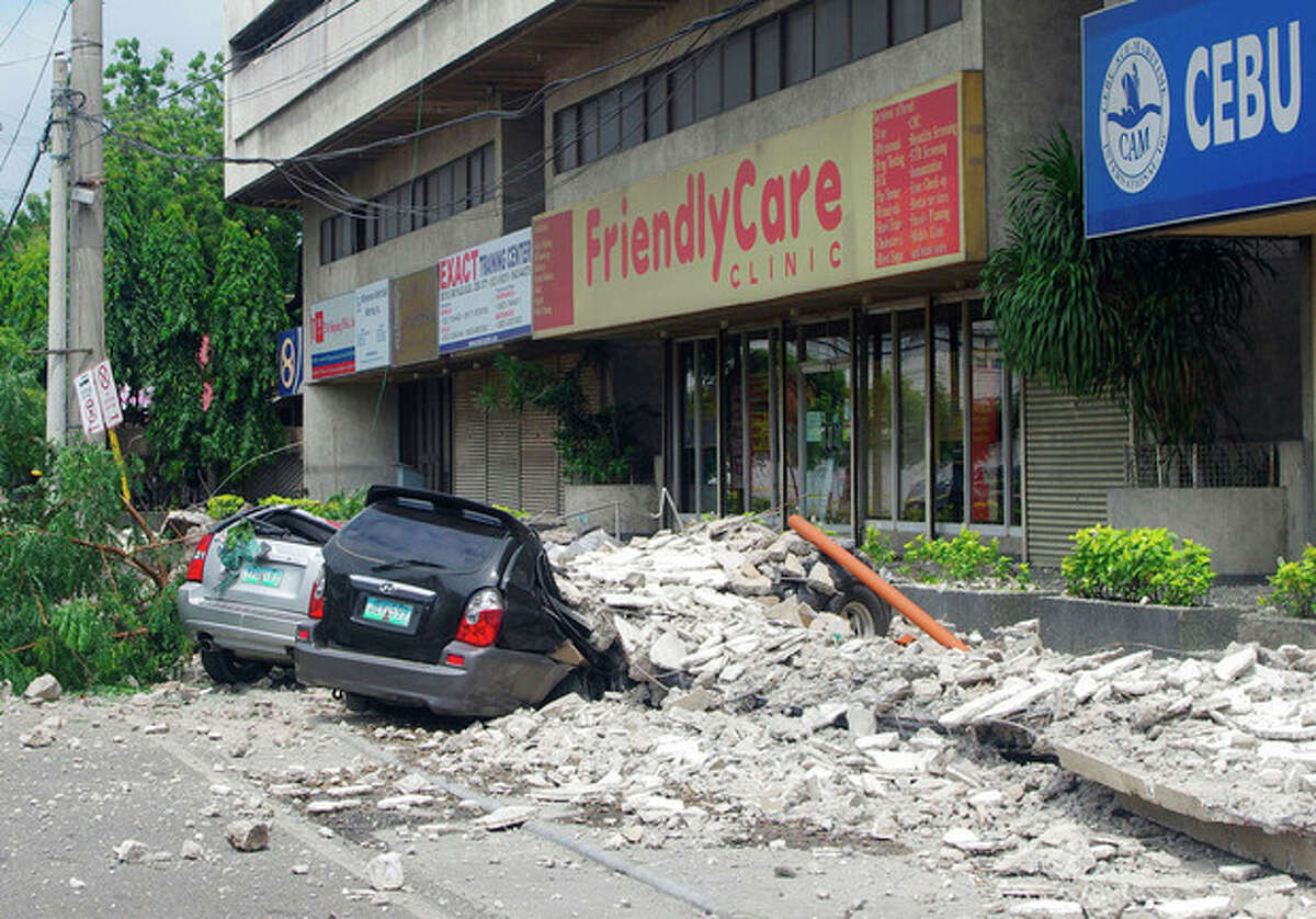 Damaged cars lie under a rubble outside the GMC Plaza Building in Cebu, central Philippines Tuesday, Oct. 15, 2013. A 7.2-magnitude earthquake collapsed buildings, cracked roads and toppled the bell tower of the Philippines' oldest church Tuesday morning, killing at least 20 people across the central region. (AP Photo/Chester Baldicantos)