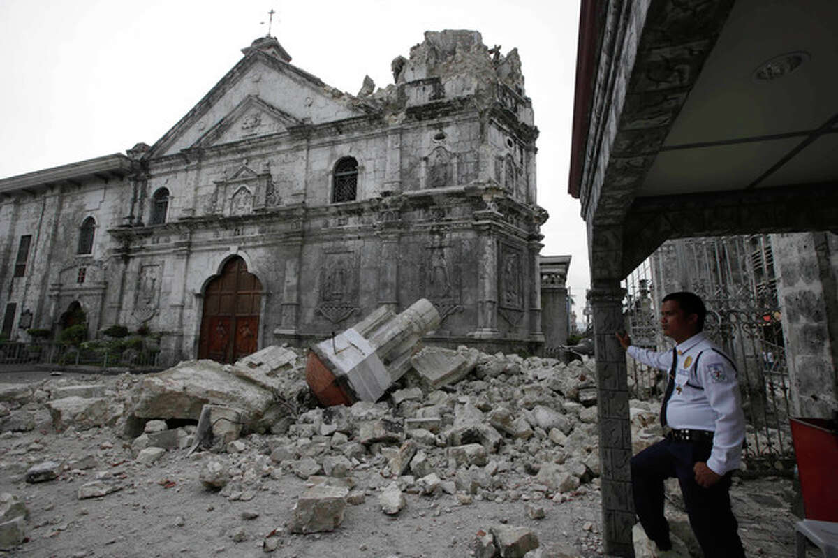 A private guard stands near the damaged Basilica of the Holy Child following a 7.2-magnitude earthquake that hit Cebu city in central Philippines and toppled the bell tower of the Philippines' oldest church Tuesday, Oct. 15, 2013. The tremor collapsed buildings, cracked roads and toppled the bell tower of the Philippines' oldest church Tuesday morning, causing multiple deaths across the central region and sending terrified residents into deadly stampedes. (AP Photo/Bullit Marquez)