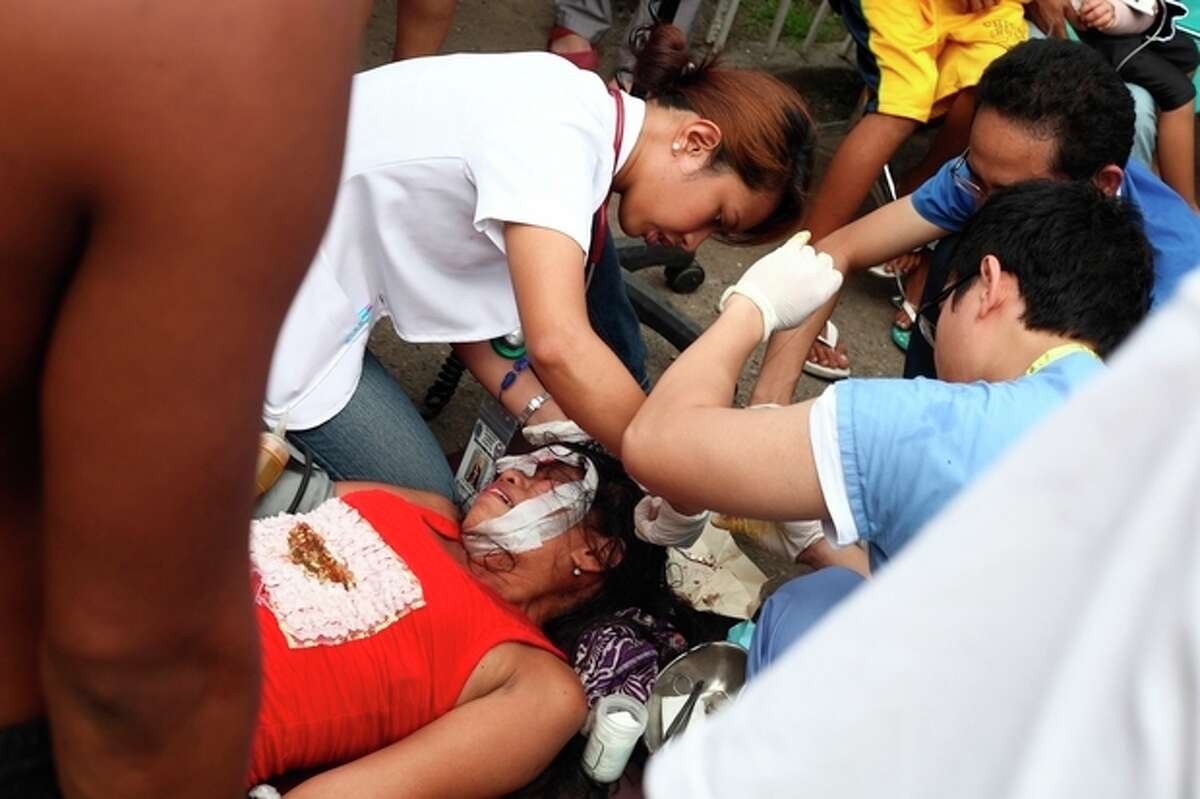 Doctors treat a woman outside a damaged Vicente Sotto Hospital in Cebu, central Philippines on Tuesday Oct. 15, 2013. A 7.2-magnitude earthquake collapsed buildings, cracked roads and toppled the bell tower of the Philippines' oldest church Tuesday morning, killing at least 20 people across the central region. (AP Photo/Chester Baldicantos)