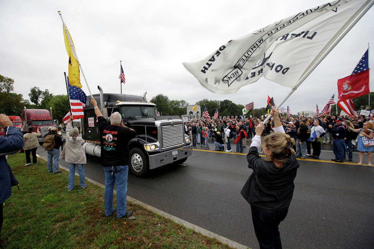 Protesters cheer as large trucks arrive at a rally at the World War II Memorial on the National Mall in Washington Sunday, Oct. 13, 2013. Leaders in the U.S. Senate have taken the helm in the search for a deal to end the partial government shutdown and avert a federal default. The rally was organized to protest the closure of the Memorial, subsequent to the shutdown, and lack of access to it by World War II veterans, who traveled there on Honor Flight visits. (AP Photo/Alex Brandon)