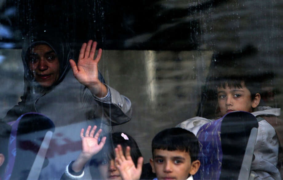 A Syrian refugee family waves to relatives after boarding a bus to Beirut International Airport for a flight to Germany where they have been accepted for temporary resettlement, at the International Organization for Migration office in Beirut, Lebanon, Thursday, Oct. 10, 2013. The dozens of Syrians heading to Germany on Thursday were the second batch of the 4,000 refugees that Germany has accepted to receive on two-year visas while Syria remains mired in a two-year civil war that has killed over 100,000 people, displaced 5 million within their own country, and prompted another 2 million people to flee the country as refugees. (AP Photo/Hussein Malla) / AP