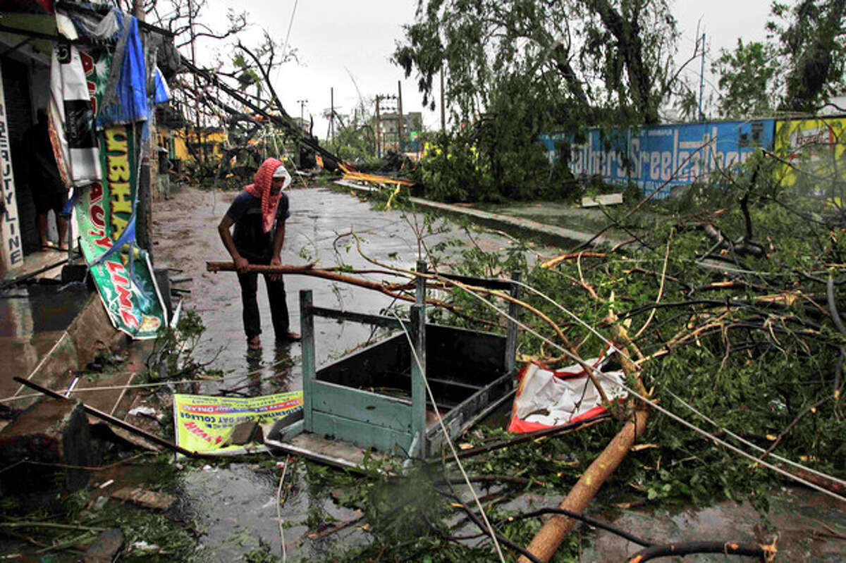 An Indian man salvages a table stuck in uprooted trees fallen during Cyclone Phailin on a road in Berhampur, India, Sunday, Oct. 13, 2013. An immense, powerful cyclone that lashed the Indian coast, forcing 500,000 people to evacuate and causing widespread damage, weakened Sunday after making landfall. Several people died in the rains that fell ahead of the storm, most killed by falling branches, Indian media reported, but the situation on the ground in many areas was still unclear after Cyclone Phailin slammed into the coast Saturday evening in Orissa state, where power and communications lines were down along much of the coastline. (AP Photo/Bikas Das)
