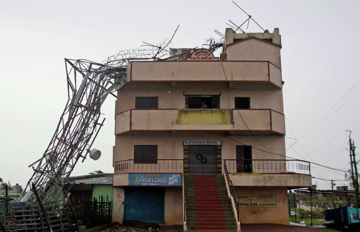 A man stands on the balcony of his house on whose top a mobile tower has fallen at the cyclone hit Humma village on the Bay of Bengal coast in Ganjam district, Orissa state, India, Sunday, Oct. 13, 2013. India began sorting through miles of wreckage Sunday after Cyclone Phailin roared ashore, flooding towns and villages and destroying tens of thousands of thatch homes, but officials said massive evacuation efforts had spared the east coast from widespread loss of life. (AP Photo/Biswaranjan Rout)