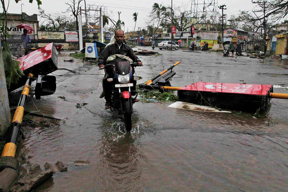 A motorcyclist rides past fallen traffic signal poles during Cyclone Phailin at a road crossing in Berhampur, India, Sunday, Oct. 13, 2013. An immense, powerful cyclone that lashed the Indian coast, forcing 500,000 people to evacuate and causing widespread damage, weakened Sunday after making landfall. Several people died in the rains that fell ahead of the storm, most killed by falling branches, Indian media reported, but the situation on the ground in many areas was still unclear after Cyclone Phailin slammed into the coast Saturday evening in Orissa state, where power and communications lines were down along much of the coastline. (AP Photo/Bikas Das) / AP