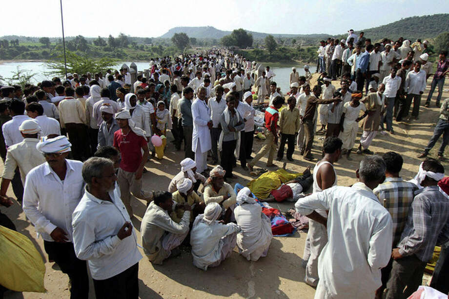 Indian villagers gather after a deadly stampede on a bridge across the Sindh River in Datia district in Madhya Pradesh state, India, Sunday, Oct. 13, 2013. A stampede by masses of Hindu worshippers left scores of people dead on a bridge they had been crossing to reach a temple in central India, police said. (AP Photo) / AP