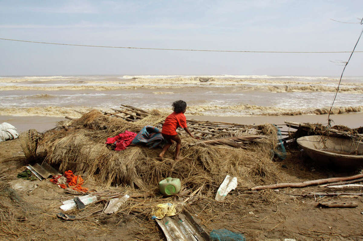 An Indian child searches for belongings amid the remains of her damaged house after returning to the cyclone hit village of Podampeta on the Bay of Bengal coast in Ganjam district, Orissa state, India, Sunday, Oct. 13, 2013. India began sorting through miles of wreckage Sunday after powerful Cyclone Phailin roared ashore, flooding towns and villages and destroying tens of thousands of thatch homes, but officials said massive evacuation efforts had spared the east coast from widespread loss of life. (AP Photo/Biswaranjan Rout)