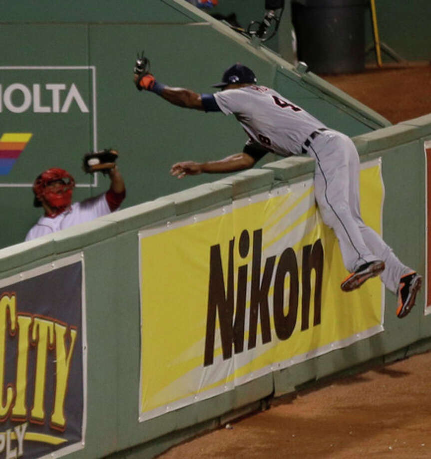 Detroit Tigers' Torii Hunter leaps and misses a catch as Boston Red Sox's David Ortiz hits a grand slam home run in the eighth inning during Game 2 of the American League baseball championship series Sunday, Oct. 13, 2013, in Boston. (AP Photo/Charlie Riedel) / AP