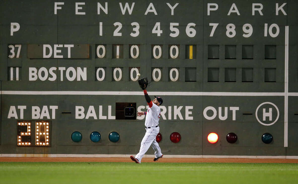 """Boston Red Sox's Jonny Gomes plays a ball off the """"Green Monster"""" hit by Detroit Tigers' Prince Fielder in the sixth inning as Fielder hits a double during Game 2 of the American League baseball championship series Sunday, Oct. 13, 2013, in Boston. (AP Photo/Elise Amendola)"""