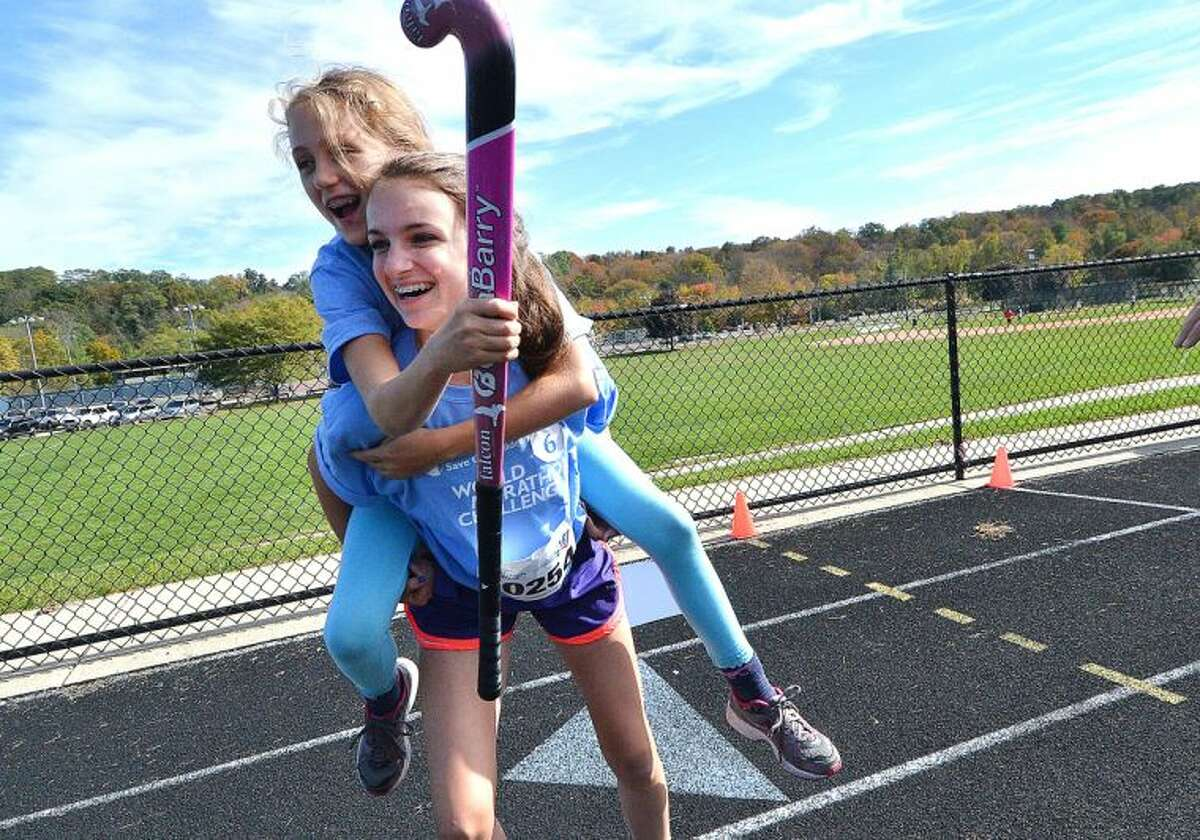 Hour Photo/Alex von Kleydorff. The World Marathon Challenge to raise funds for International relief and the development agency Save The Children had Wilton atheletes compete in a relay at the Wilton High School track. Here Field hockey player Olivia DeLuca trys her leg piggyback with Alexandra Varoli-Grace.