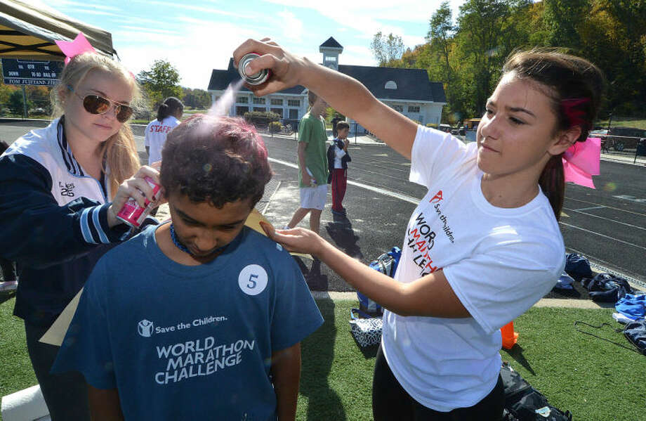 Hour Photo/Alex von Kleydorff. Wilton cheerleaders Lydia Bates and Christina Caratozzolo give Clyde Tinnen a fresh coat of pink paint on his hair, during The World Marathon Challenge to raise funds for International relief and the development agency Save The Children which had Wilton atheletes compete in a relay at the Wilton High School track.