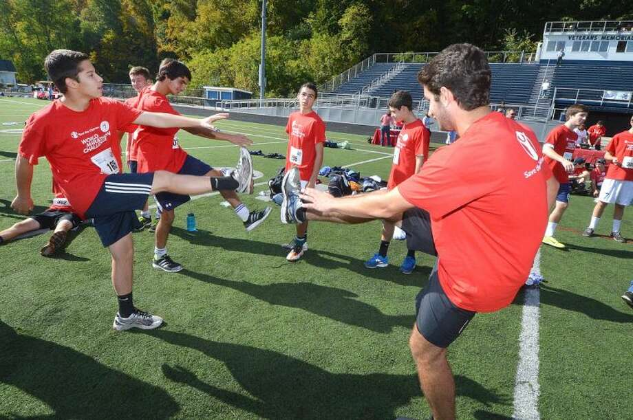 Hour Photo/Alex von Kleydorff. Alex Lord and Troy Lamson warm up with othere atheletes before The World Marathon Challenge to raise funds for International relief and the development agency Save The Children which had Wilton atheletes compete in a relay at the Wilton High School track.