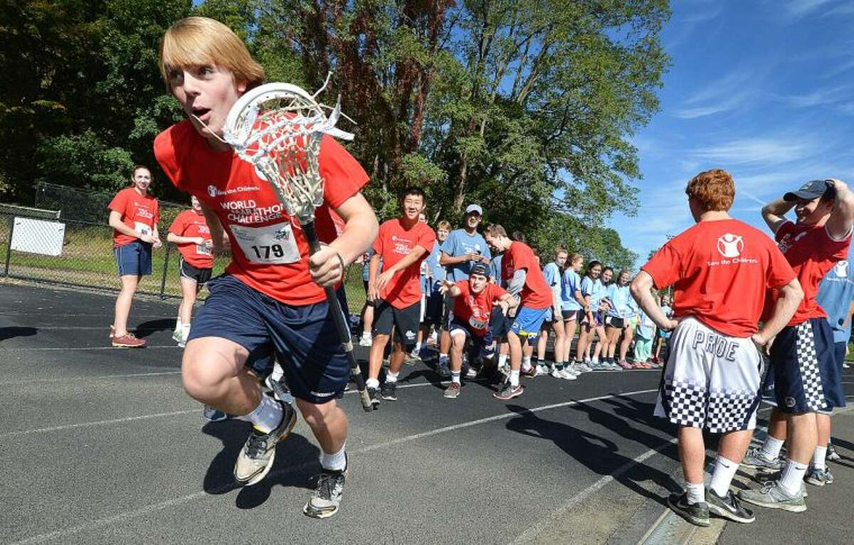 Hour Photo/Alex von Kleydorff. Lacrosse player Christian Hansson grabs the baton, stick , and takes off during The World Marathon Challenge to raise funds for International relief and the development agency Save The Children which had Wilton atheletes compete in a relay at the Wilton High School track.
