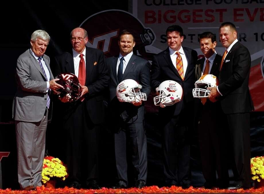 """From left, Virginia Tech head football coach Frank Beamer, Virginia Tech athletic director Jim Weaver, Marcus Smith, president of Speedway Motorsports, Jerry Caldwell, general manager of Bristol Motor Speedway, Tennessee athletic director, Dave Hart, and Tennessee head football coach Butch Jones pose after a press conference at Bristol Motor Speedway Monday, Oct. 14, 2013, in Bristol, Tenn. Tennessee and Virginia Tech will finally play a football game at Bristol Motor Speedway in what is being billed as the """"Battle of Bristol."""" (AP Photo/Wade Payne) / FR23601 AP"""