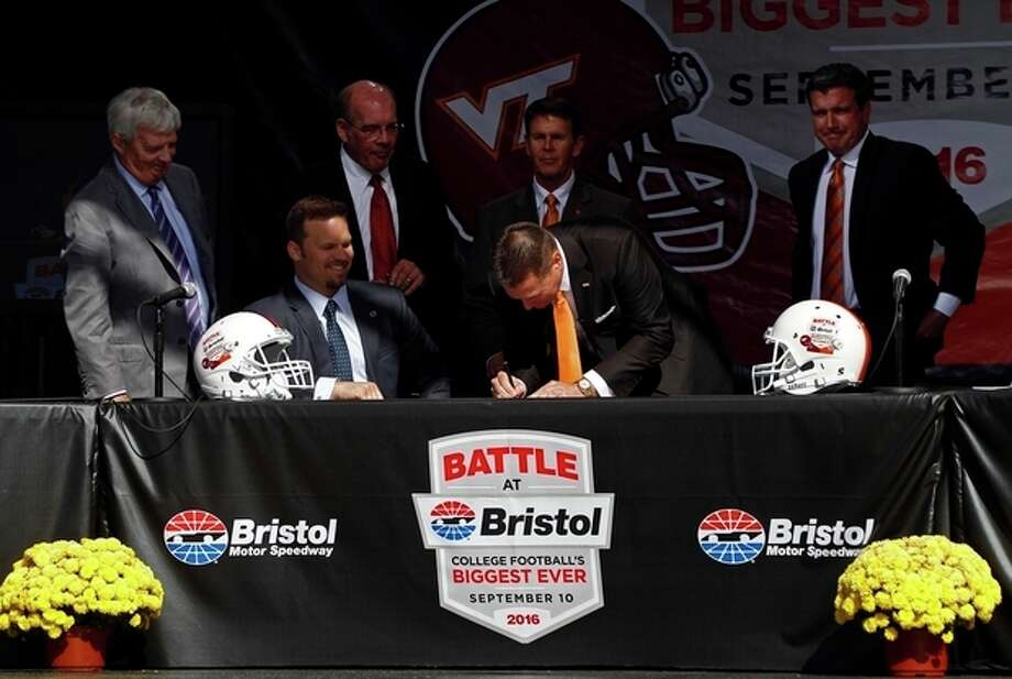 "Tennessee head football coach Butch Jones signs the contract as Marcus Smith, president of Speedway Motorsports, seated, Virginia Tech head football coach Frank Beamer, standing at left, Virginia Tech athletic director Jim Weaver, second from left, Tennessee athletic director Dave Hart, second from right, and Jerry Caldwell, general manager of Bristol Motor Speedway, right, watch during a press conference at Bristol Motor Speedway Monday, Oct. 14, 2013, in Bristol, Tenn. Tennessee and Virginia Tech will finally play a football game at Bristol Motor Speedway in what is being billed as the ""Battle of Bristol."" (AP Photo/Wade Payne) / FR23601 AP"