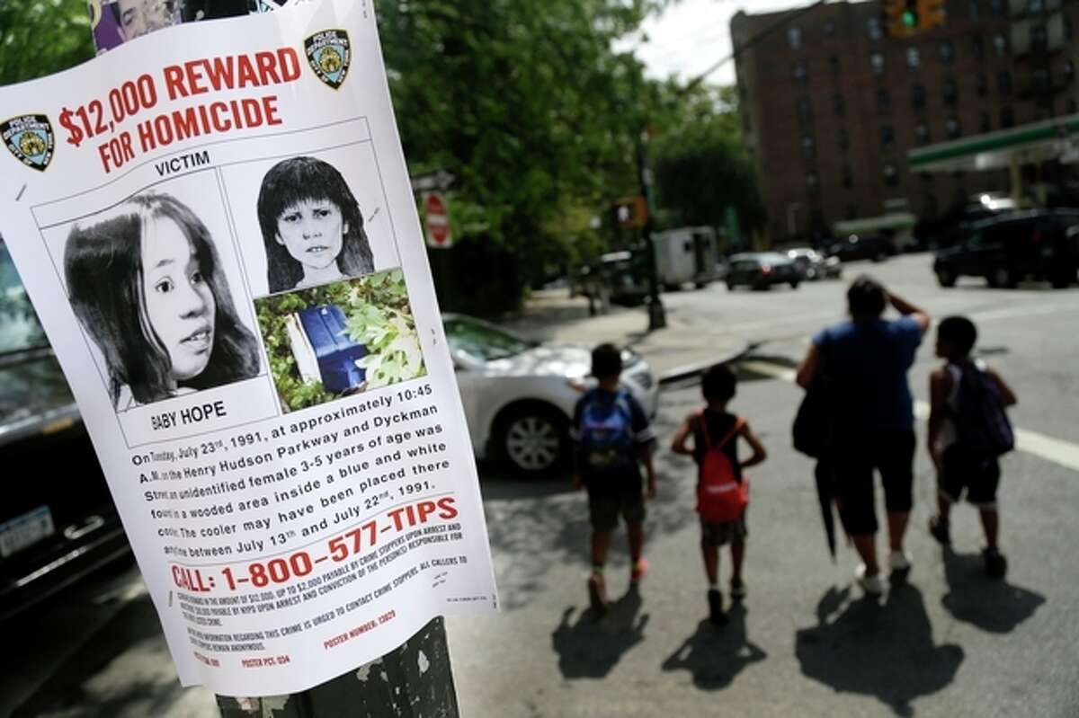 FILE - In this July 23, 2013, file photo shows a poster soliciting information regarding an unidentified body near the site where the body was found in New York. Police in New York City said Saturday, Oct. 12, 2013, that they had arrested the killer of a child who was nicknamed Baby Hope by detectives after her body was discovered inside a picnic cooler beside a Manhattan highway in 1991.(AP Photo/Seth Wenig, File)