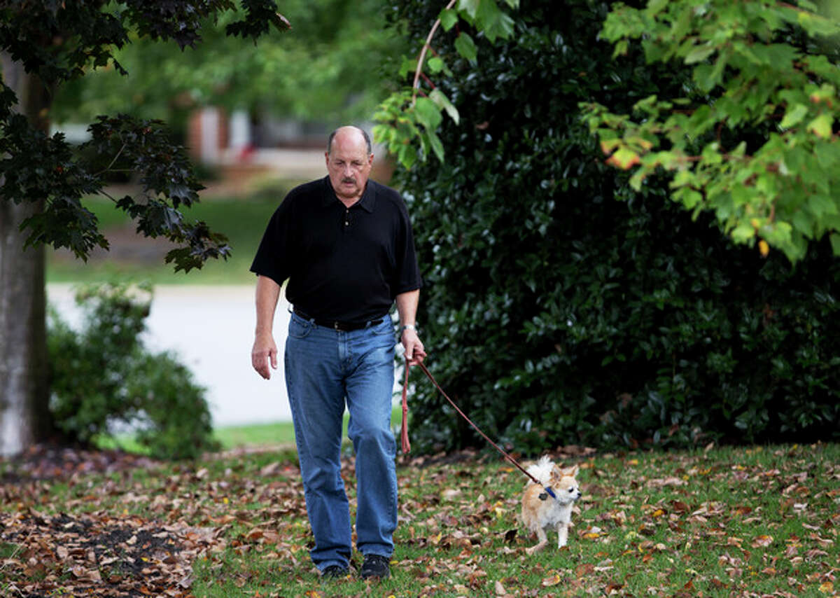 In this Wednesday, Oct. 9, 2013 photo, graphic designer Tom Sadowski, 65, who delayed his retirement, walks his dog near his home in Sterling, Va. Older Americans appear to have accepted the reality of a retirement that comes later in life and no longer represents a complete exit from the workforce. Some 82 percent say it is at least somewhat likely they will work for pay in retirement, a poll by the Associated Press-NORC Center for Public Affairs Research finds. (AP Photo/Manuel Balce Ceneta)