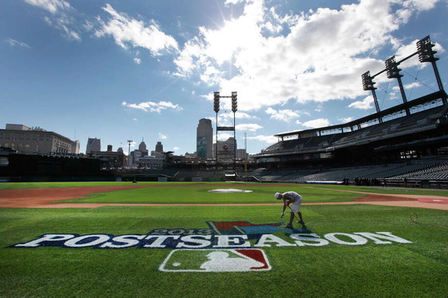 Kyle Pickens paints a postseason logo on the field at Comerica Park before practice for Game 3 of the American League baseball championship series between the Detroit Tigers and Boston Red Sox in Detroit, Monday, Oct. 14, 2013. (AP Photo/Paul Sancya) / AP