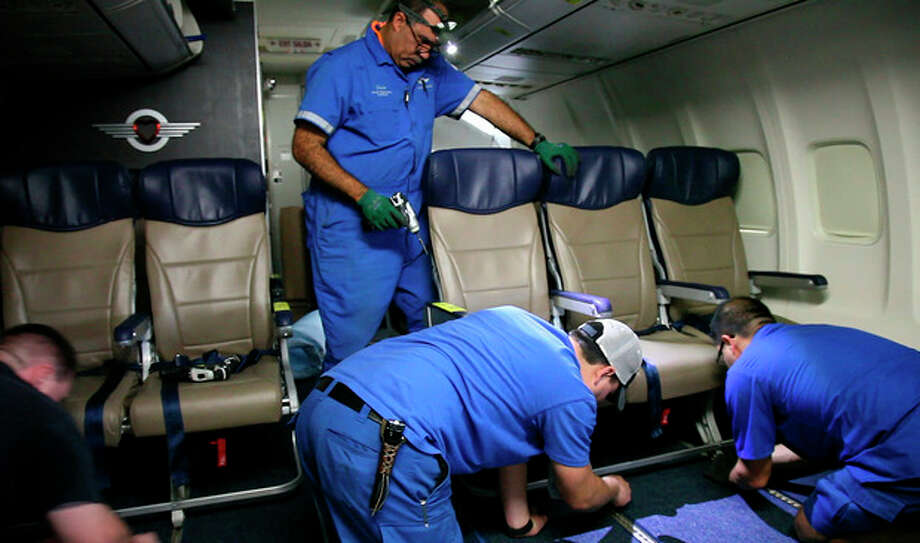 In this Sept. 23, 2013 photo, Southwest Airlines aircraft technicians install newer, skinnier seats on a 737 at the carrier's headquarters in Dallas. Southwest says passengers will have the same amount of legroom even though the new seats allow for another row onboard. (AP Photo/John Mone) / AP