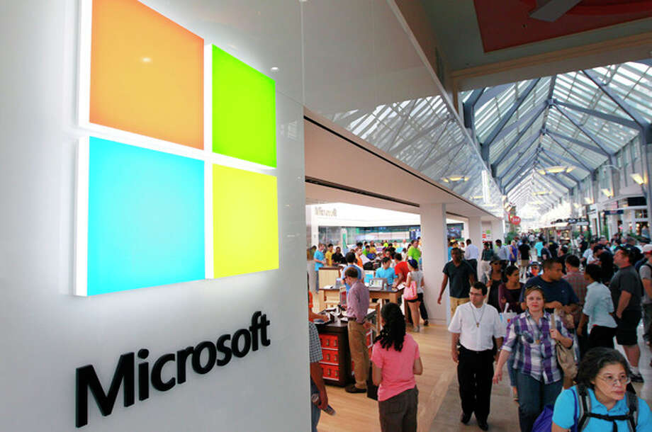 FILE - In this Thursday, Aug. 23, 2012, file photo, a new Microsoft Corp. logo, left, is seen on an exterior wall of a new Microsoft store inside the Prudential Center mall, in Boston. Microsoft is updating its Windows software for cellphones to accommodate larger devices and make it easier for motorists to reduce distractions while driving. (AP Photo/Steven Senne, File) / AP
