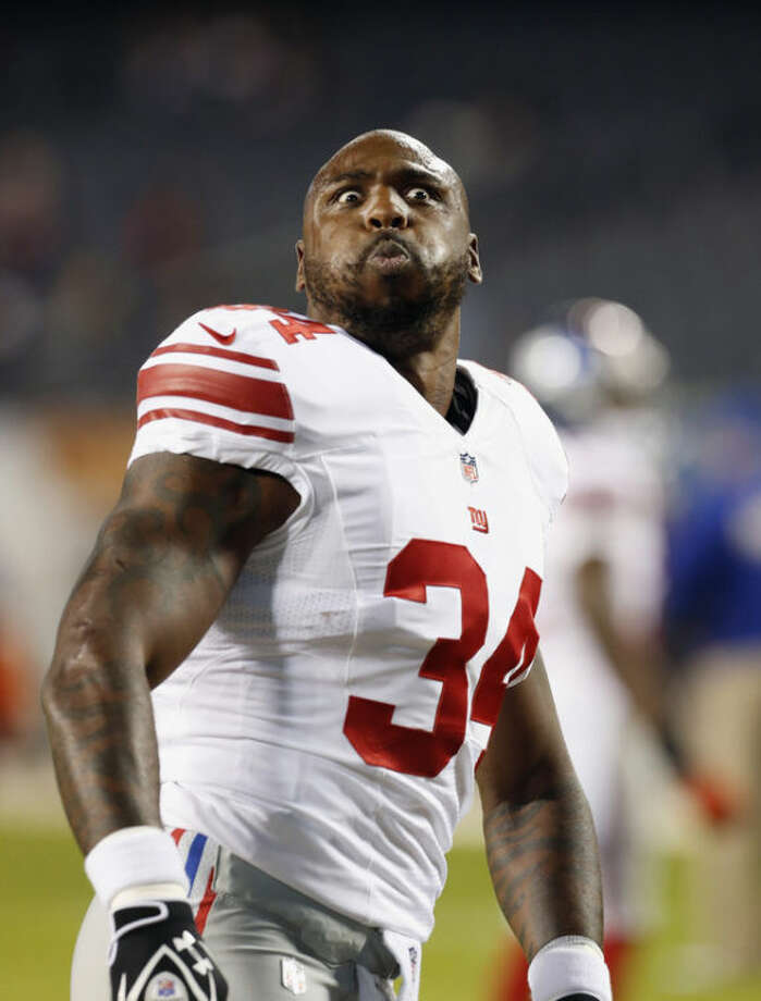 New York Giants running back Brandon Jacobs makes a face at fans before the Giants' NFL football game against the Chicago Bears, Thursday, Oct. 10, 2013, in Chicago. (AP Photo/Charles Rex Arbogast)