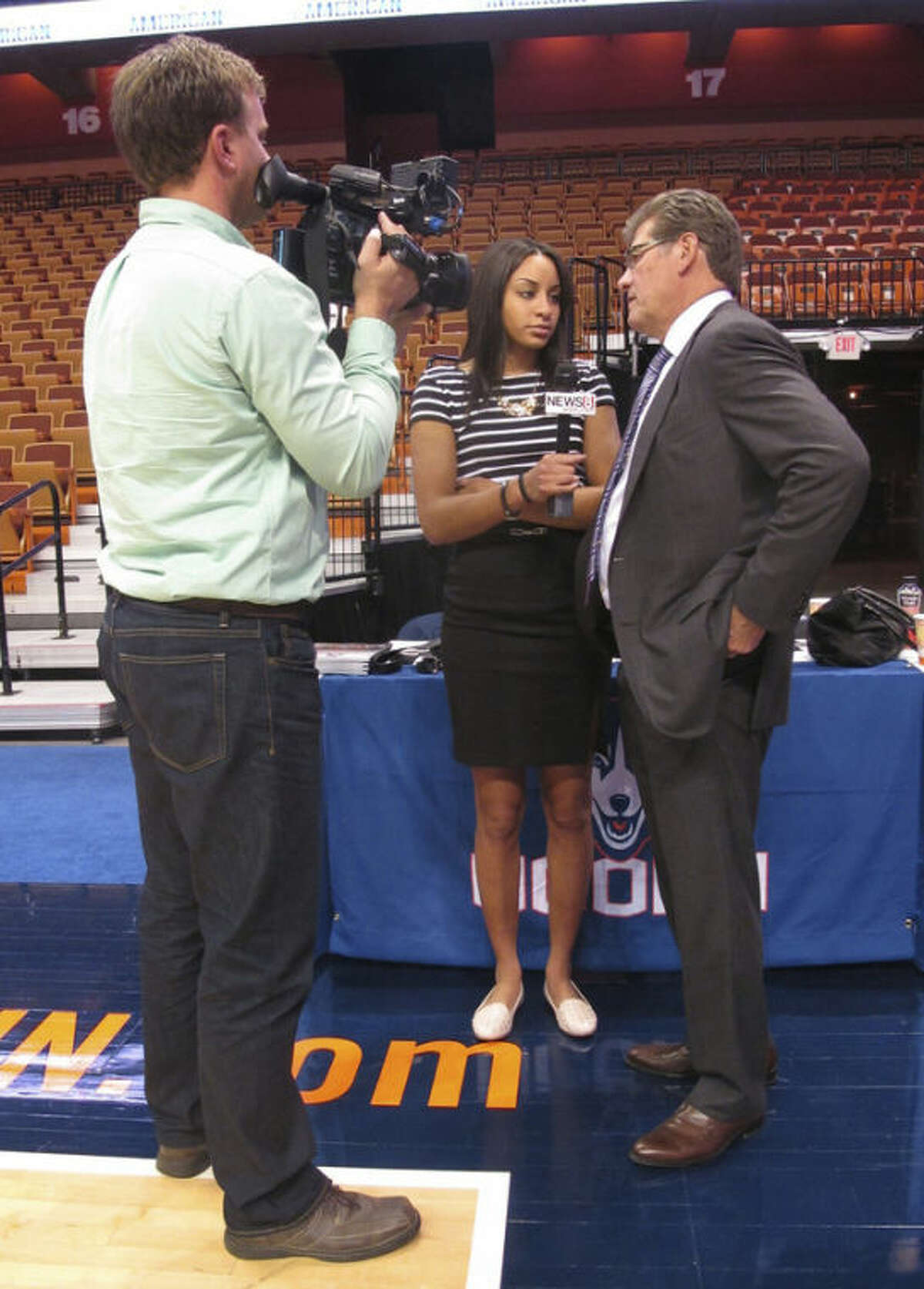 Connecticut women's basketball guard Bria Hartley, center, plays interviewer with coach Geno Auriemma, right, during the American Athletic Conference's women's basketball inaugural media day on Monday, Oct. 14, 2013 at the Mohegan Sun Arena in Uncasville, Conn. (AP Photo/Pat Eaton-Robb)