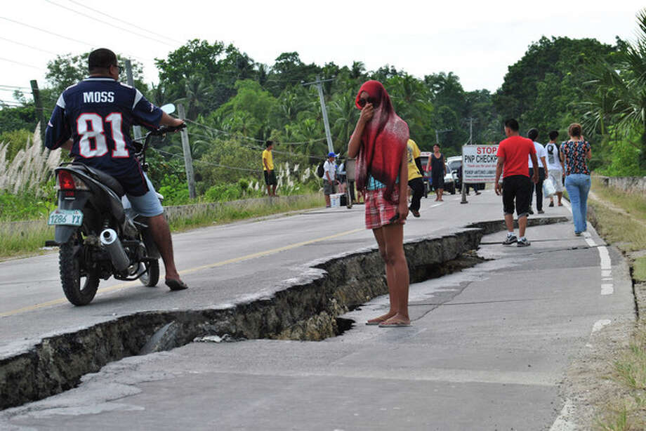 Residents walk along a damaged road following a 7.2-magnitude earthquake that hit Bohol, central Philippines, Tuesday, Oct. 15, 2013. The tremor collapsed buildings, cracked roads and toppled the bell tower of the Philippines' oldest church Tuesday morning, causing multiple deaths across the central region and sending terrified residents into deadly stampedes. (AP Photo) / AP