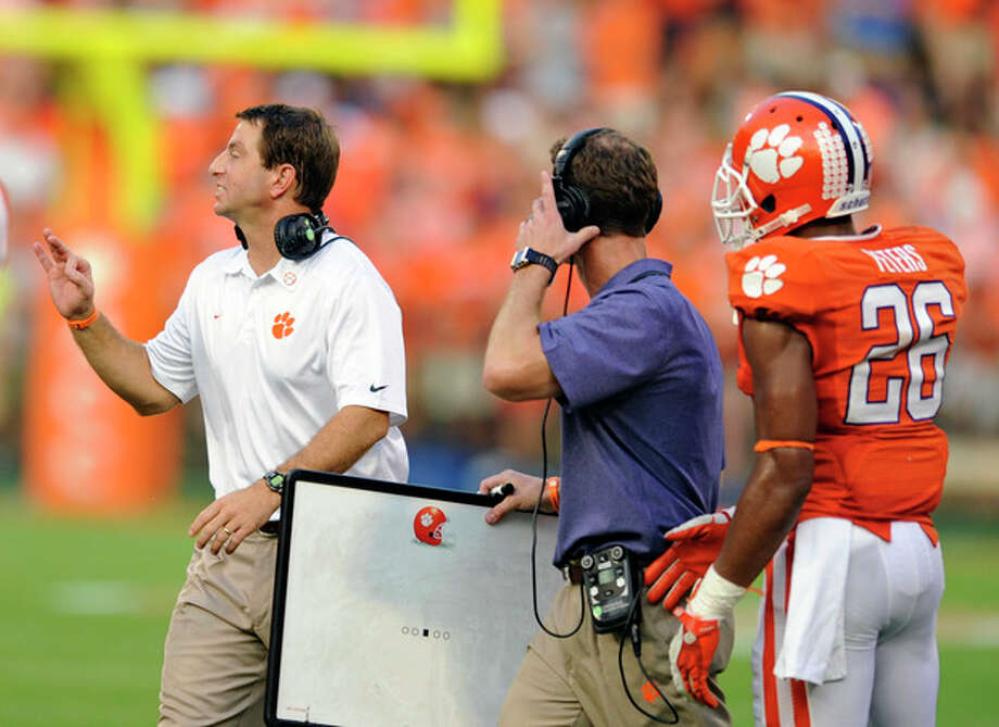 Clemson head coach Dabo Swinney, left, calls out a play to his team while defensive coordinator Brent Venables, center, and Garry Peters watch during the second half of an NCAA college football game against Boston College, Saturday, Oct. 12, 2013, at Memorial Stadium in Clemson, S.C. Clemson won 24-14. (AP Photo/ Richard Shiro) / FR159523 AP