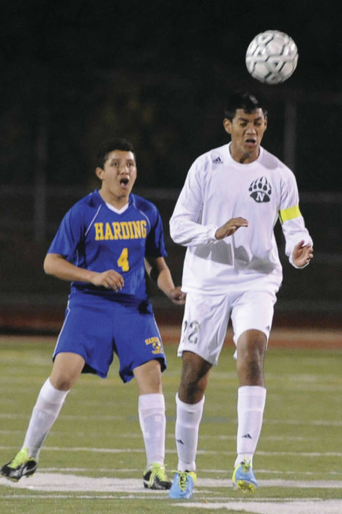 Hour photo/Matthew Vinci Norwalk's Sergio Mandujano, right, heads the ball in front of Kevin Rodriguez of Harding during Tuesday night's contest. The Bears scored three times in the first half and went on to a 4-1 win over the Presidents.