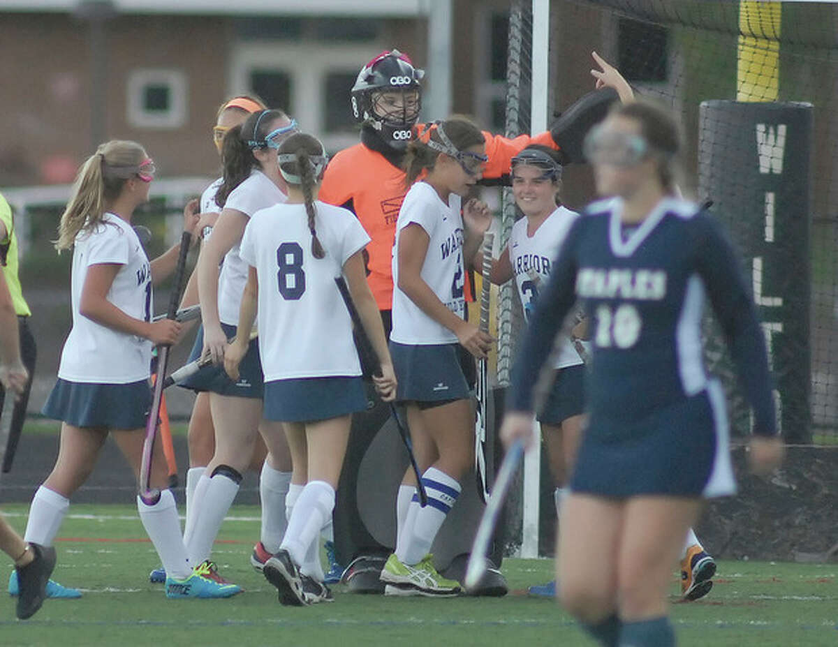 Hour photo/John Nash Wilton goaltender Lizette Roman-Johnston, center, is mobbed by teammates after making a penalty stroke save during the first half of Tuesday's FCIAC field hockey game in Wilton. The Warriors claimed a 2-0 victory.