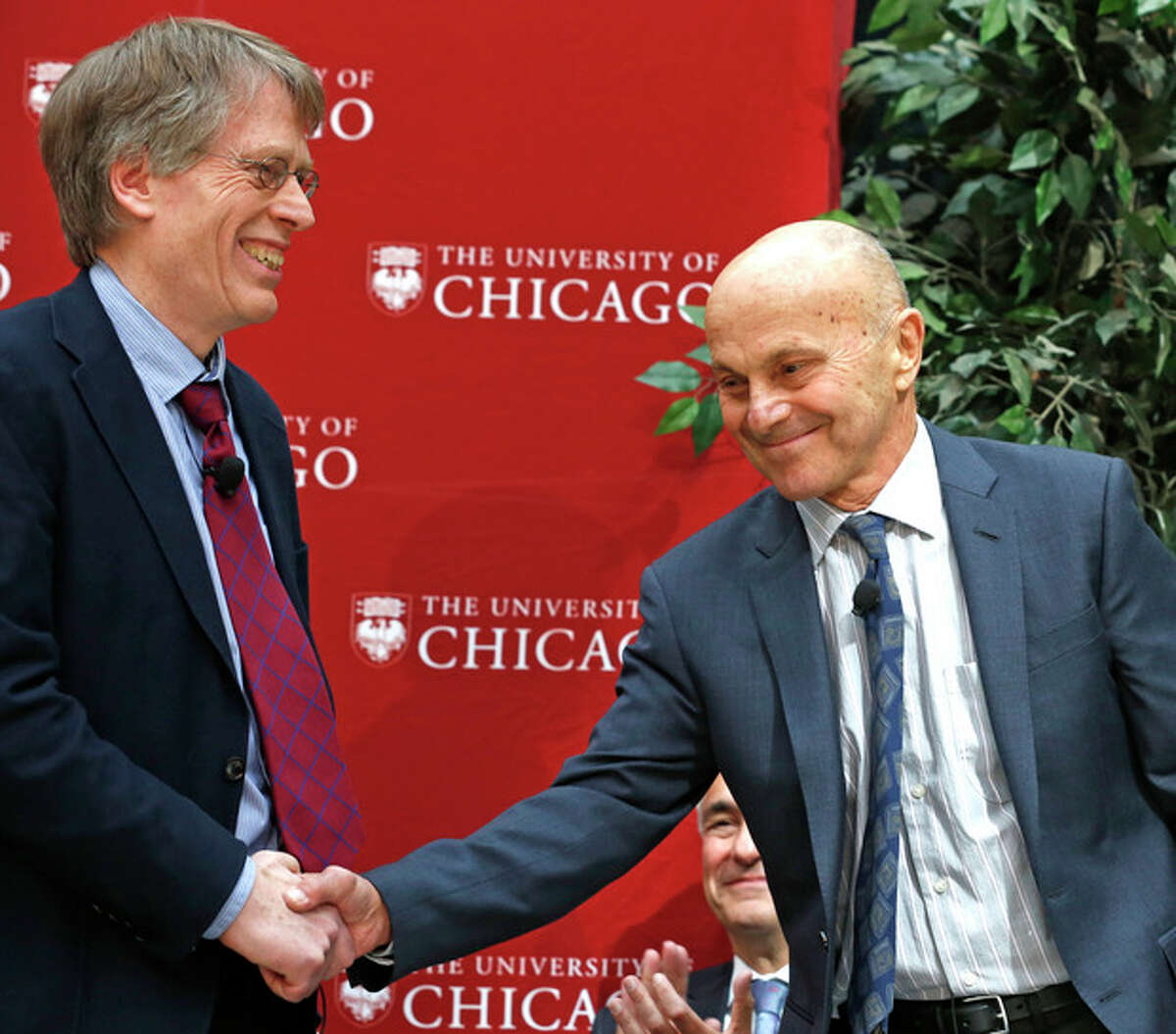 Nobel Prize winners Lars Peter Hansen, 60, left, and Eugene Fama, 74, of the University of Chicago, shake hands at a news conference Monday, Oct. 14, 2013, in Chicago after being named two of the three winners of the Nobel prize for economics. They share the prize with Robert Shiller, 67, of Yale University. (AP Photo/M. Spencer Green)