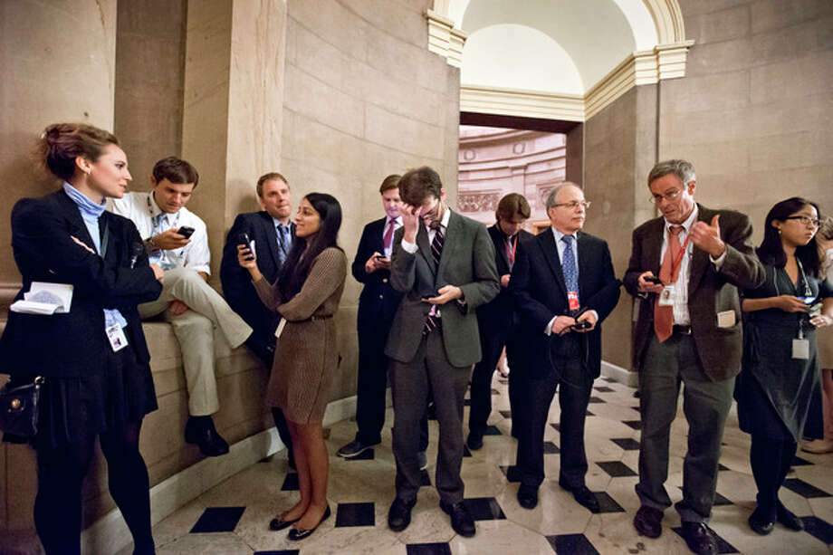 Reporters wait outside the office of Speaker of the House John Boehner, R-Ohio, as a planned vote in the House of Representatives collapsed, Tuesday night, Oct. 15, 2013, at the Capitol in Washington. Time growing desperately short, House Republicans pushed for passage of legislation late Tuesday to prevent a threatened Treasury default, end a 15-day partial government shutdown and extricate divided government from its latest brush with a full political meltdown. (AP Photo/J. Scott Applewhite) / AP