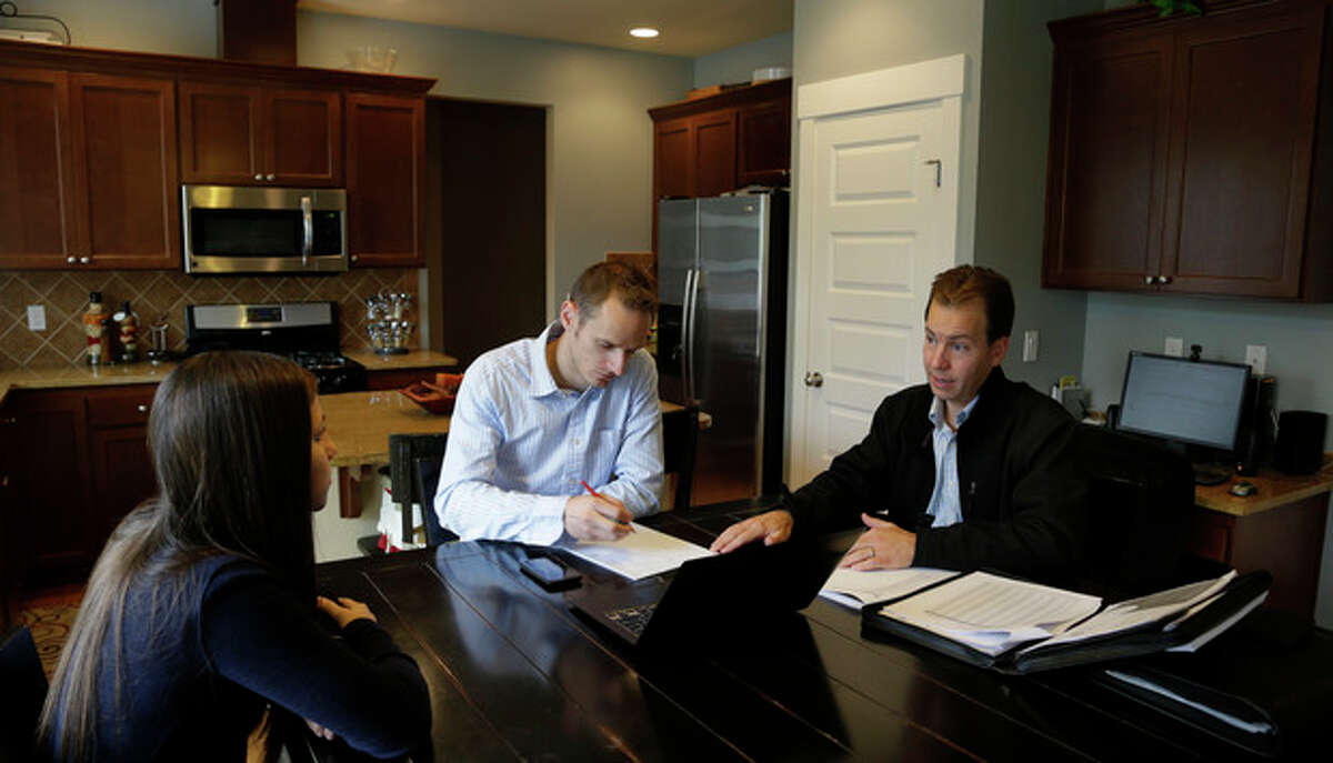 In this Thursday, Oct. 10, 2013 photo, insurance broker Jeff Lindstrom, right, meets with Brandi and Darren Litchfield to discuss health insurance plan options, at their home in the Seattle suburb of Bothell, Wash. Darren works for a startup company that doesn't yet offer an employee insurance plan, so they invited Lindstrom to outline the options of different healthcare plans that he offers as a broker. (AP Photo/Ted S. Warren)