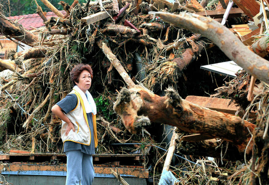 A woman looks at the aftermath of landslides in the rubble of smashed houses in Oshima after a powerful typhoon hit Izu Oshima island, about 120 kilometers (75 miles) south of Tokyo Wednesday morning, Oct. 16, 2013. Typhoon Wipha triggered landslides and caused multiple deaths on the Japanese island, before sweeping up the country's east coast, grounding hundreds of flights and paralyzing public transportation in Tokyo during Wednesday morning's rush hour. (AP Photo/Kyodo News) JAPAN OUT, CREDIT MANDATORY / Kyodo News