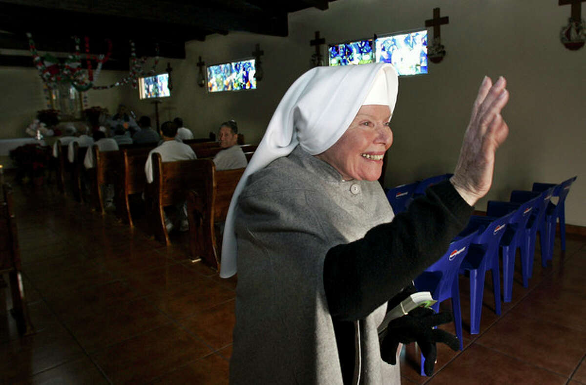 """FILE - In this Dec. 15, 2005 file photo, Sister Antonia Brenner, 79, known as the """"prison angel,"""" waves as she leaves the chapel at the La Mesa State Penitentiary in Tijuana, Mexico. Brenner died Thursday Oct. 17, 2013 after a long illness. She was 86. (AP Photo/Lenny Ignelzi, file)"""
