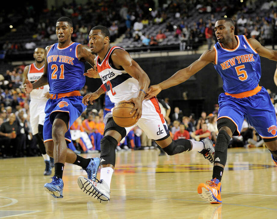 Washington Wizards guard John Wall (2) drives up court against New York Knicks guard Iman Shumpert (21) and Tim Hardaway Jr. (5) during the first half of an NBA preseason basketball game, Thursday, Oct. 17, 2013, in Baltimore. (AP Photo/Nick Wass) / FR67404 AP