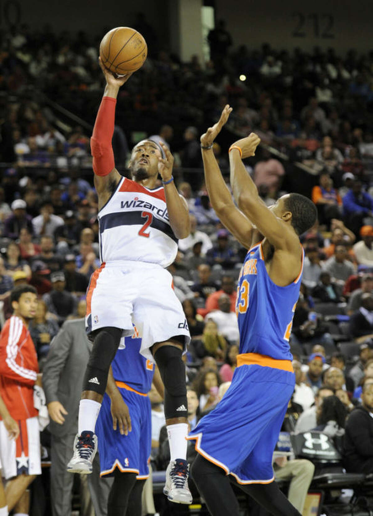 Washington Wizards point guard John Wall (2) takes a shot against New York Knicks shooting guard Toure' Murry (23) during the first half of an NBA preseason basketball game, Thursday, Oct. 17, 2013, in Baltimore. (AP Photo/Nick Wass)