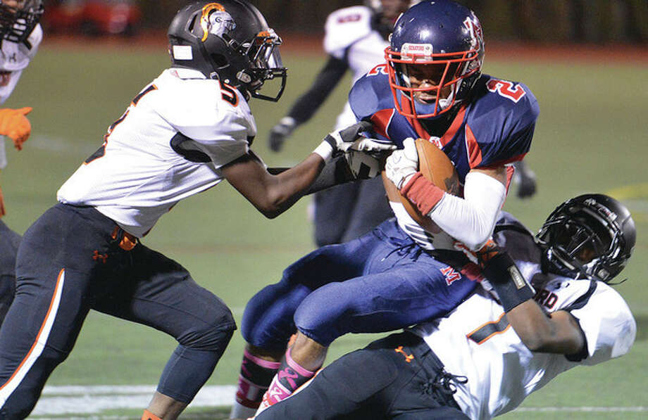 Hour photos/Alex von KleydorffBrien McMahon's Malik Whittaker, center, hangs on to the ball after making a reception between two Stamford defenders during Friday night's game. The Senators turned back the visiting Black Knights, 39-6.