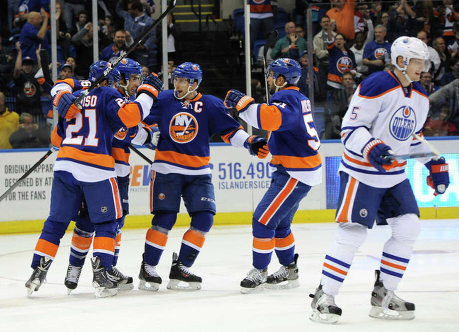 New York Islanders' Kyle Okposo (21), Matt Moulson (26), John Tavares (91) and Frans Nielsen (51) celebrates Okposo's goal as Edmonton Oilers' Ladislav Smid (5) skates away in the second period of an NHL hockey game on Thursday, Oct. 17, 2013, in Uniondale, N.Y. (AP Photo/Kathy Kmonicek) / FR170189 AP