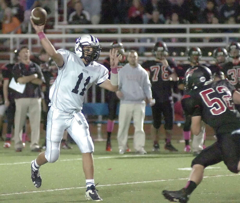 Hour photo/John NashWilton quarterback Brett Phillips (11) fires a pass before Fairfield Warde defender Wade Petro can close in during Friday's game in Fairfield. The Mustangs handed the visiting Warriors a 35-21 defeat.