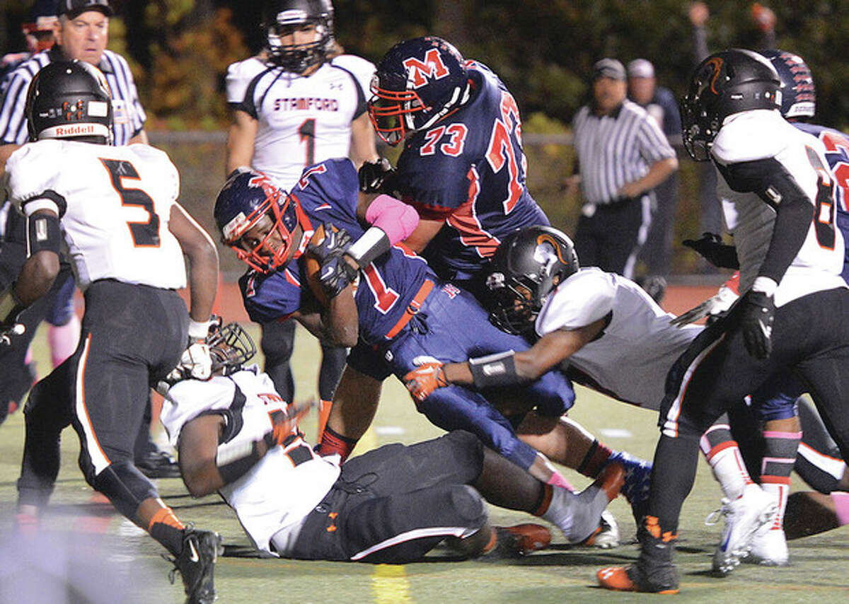 Hour photo/Alex von Kleydorff Brien McMahon's Kentrell Snider (7) battles his way into the end zone to score the Senators' first touchdown in Friday night's game against Stamford at Casagrande Field. Unbeaten McMahon scored its sixth straight victory, a 39-6 conquest of the Black Knights.