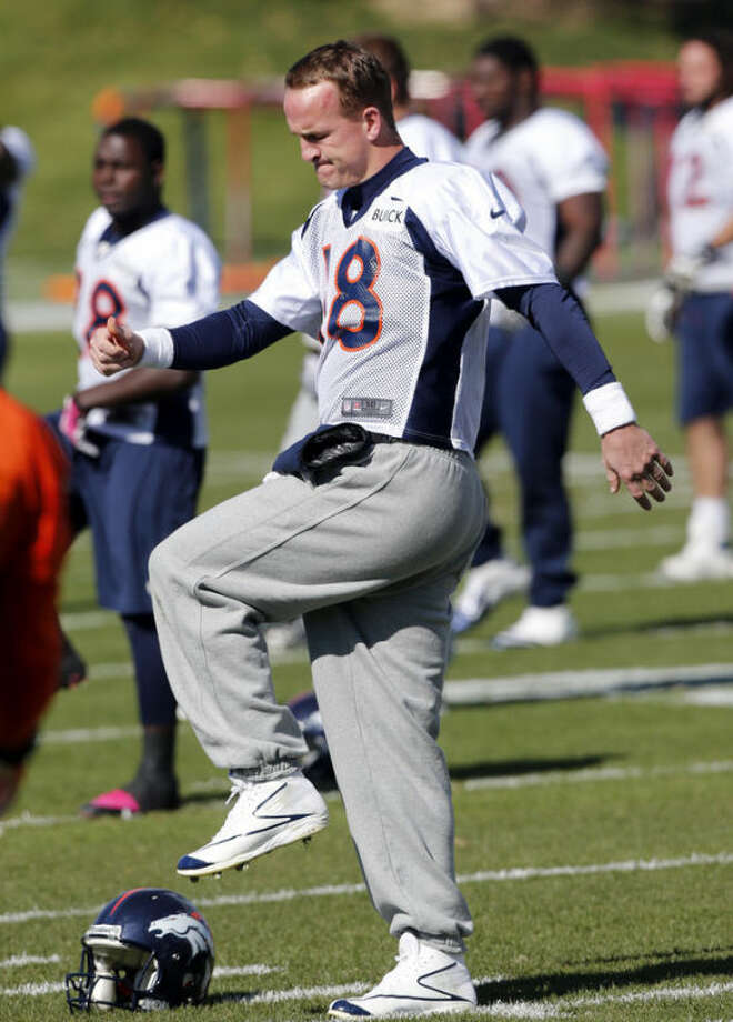 Denver Broncos quarterback Peyton Manning warms up at at the NFL football team's practice facility in Englewood, Colo., on Wednesday, Oct. 16, 2013. Manning is expected to lead the Broncos against the Indianapolis Colts this Sunday. (AP Photo/Ed Andrieski)