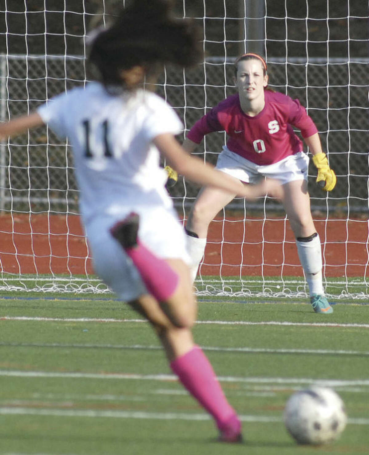Hour photo/John Nash - Mary Bennwitz, right, the goalkeeper at Staples High School, keeps her eye on a shot take by a Norwalk player last week.