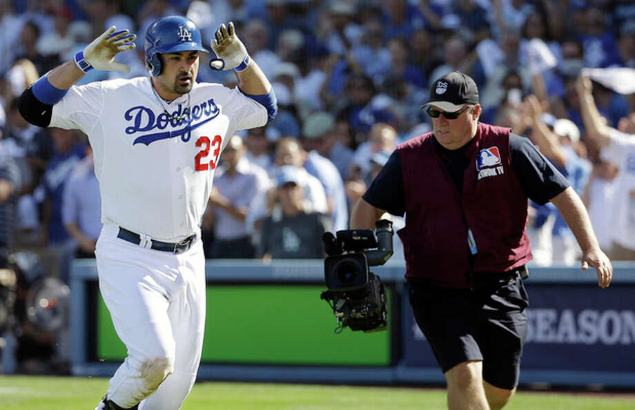 Los Angeles Dodgers' Adrian Gonzalez celebrates after hitting a home run during the third inning of Game 5 of the National League baseball championship series against the St. Louis Cardinals Wednesday, Oct. 16, 2013, in Los Angeles. (AP Photo/David J. Phillip) / AP