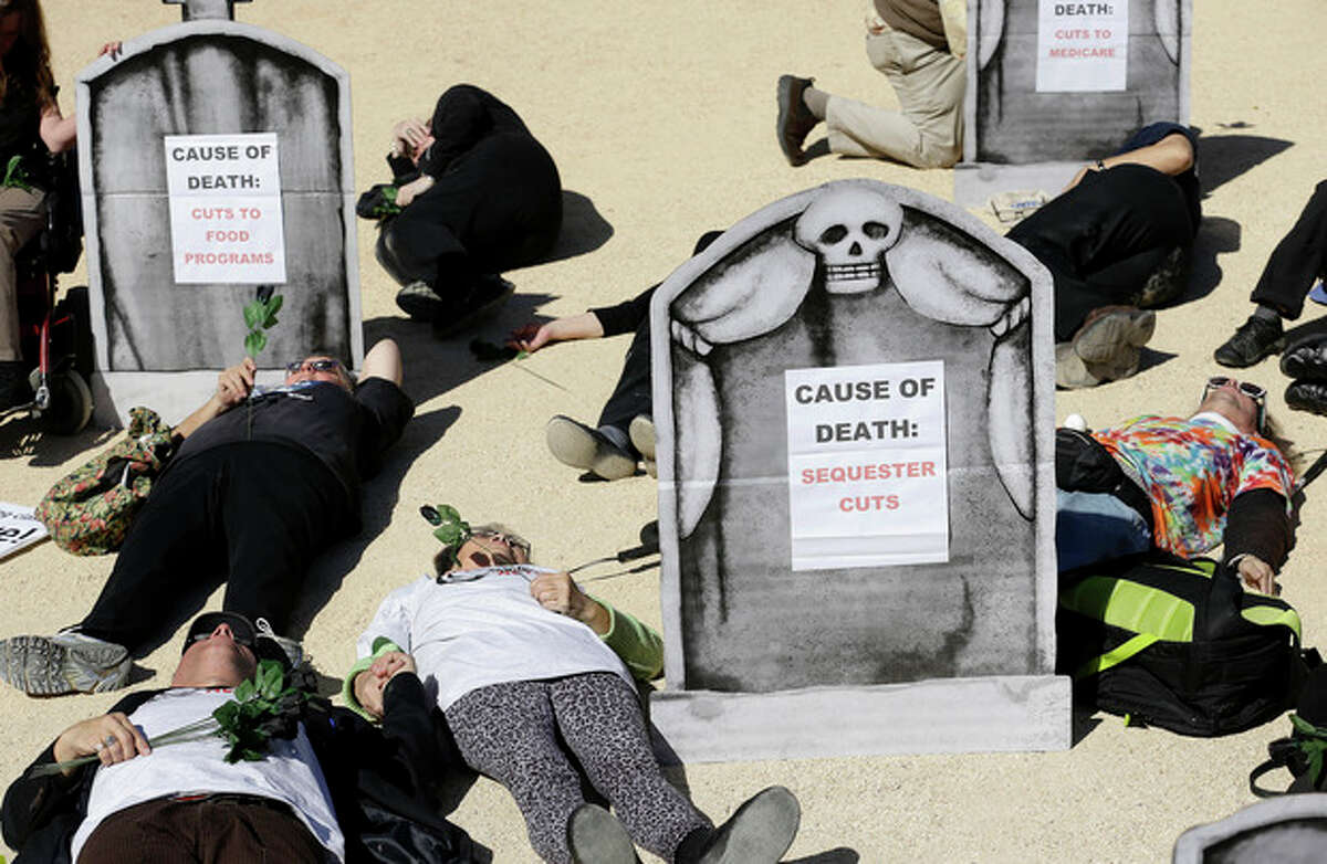 """Activists perform a """"Die In"""" to protest government shutdown and proposed cuts to Medicare, Social Security benefits, as well as child care, food, disability, and senior advocate programs outside of the federal building in San Francisco, Wednesday, Oct. 16, 2013. (AP Photo/Jeff Chiu)"""