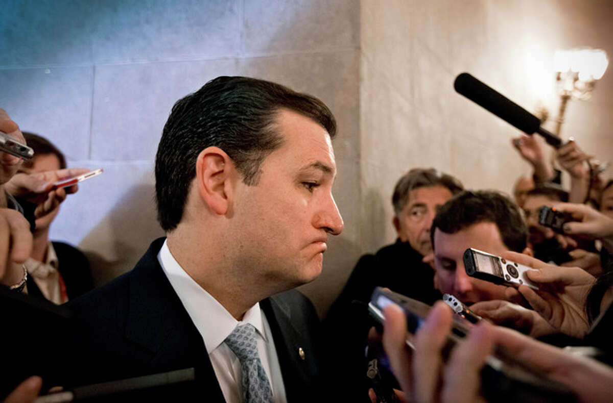 Sen. Ted Cruz, R-Texas, speaks to reporters waiting outside a closed-door meeting of Senate Republicans as news emerged that leaders reached a last-minute agreement to avert a threatened Treasury default and reopen the government after a partial, 16-day shutdown, at the Capitol in Washington, Wednesday, Oct. 16, 2013. Cruz said he would not try to block the agreement. (AP Photo/J. Scott Applewhite)