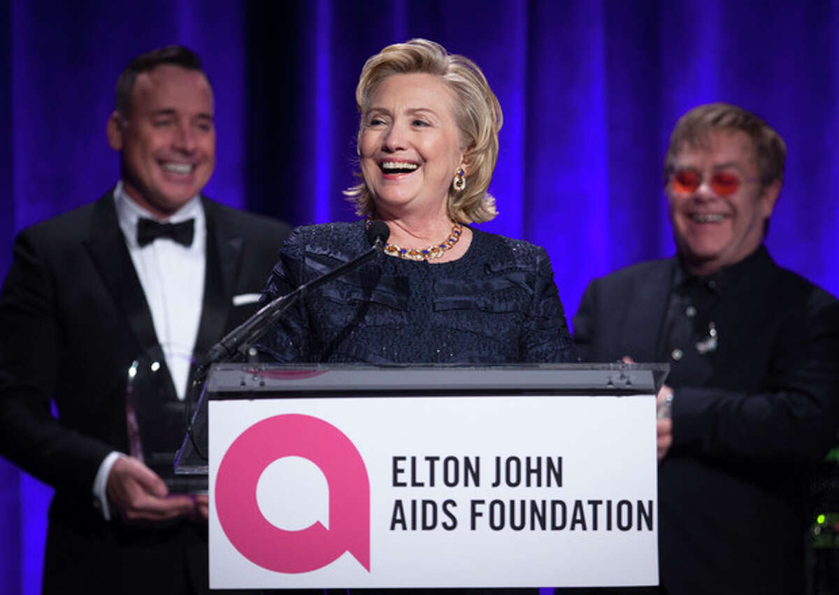 """Former Secretary of State Hillary Clinton speaks as Elton John ( R) and his partner David Furnish (L) look on, after receiving her Founders award during the Elton John AIDS Foundation's 12th Annual """"An Enduring Vision"""" benefit gala at Cipriani Wall Street on Tuesday, Oct. 15, 2013 in New York. (Photo by Carlo Allegri/Invision/AP)"""