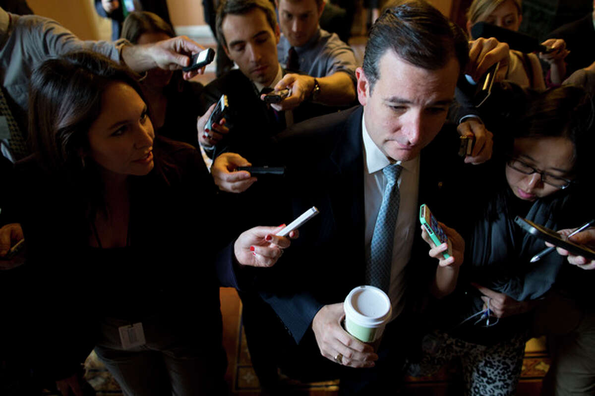 Sen. Ted Cruz, R-Texas, is followed by reporters as he walks to a Senate GOP meeting on Capitol Hill on Wednesday, Oct. 16, 2013 in Washington. The partial government shutdown is in its third week and less than two days before the Treasury Department says it will be unable to borrow and will rely on a cash cushion to pay the country's bills. (AP Photo/ Evan Vucci)