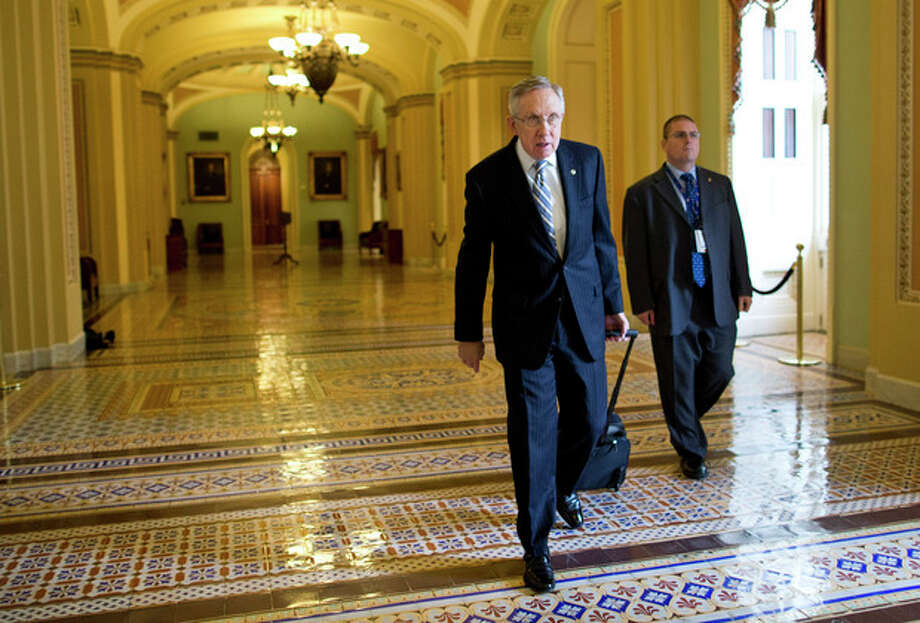 Senate Majority Leader Sen. Harry Reid, D-Nev., walks to his office after arriving on Capitol Hill on Wednesday, Oct. 16, 2013 in Washington. Aides to Senate Democrat Majority Leader Harry Reid and Republican Minority Leader Mitch McConnell said the leaders resumed talks Tuesday night and voiced optimism about striking an agreement Wednesday that could pass both houses of Congress and reach President Barack Obama's desk before Thursday, when the U.S. Treasury says it will begin running out of cash. (AP Photo/ Evan Vucci) / AP