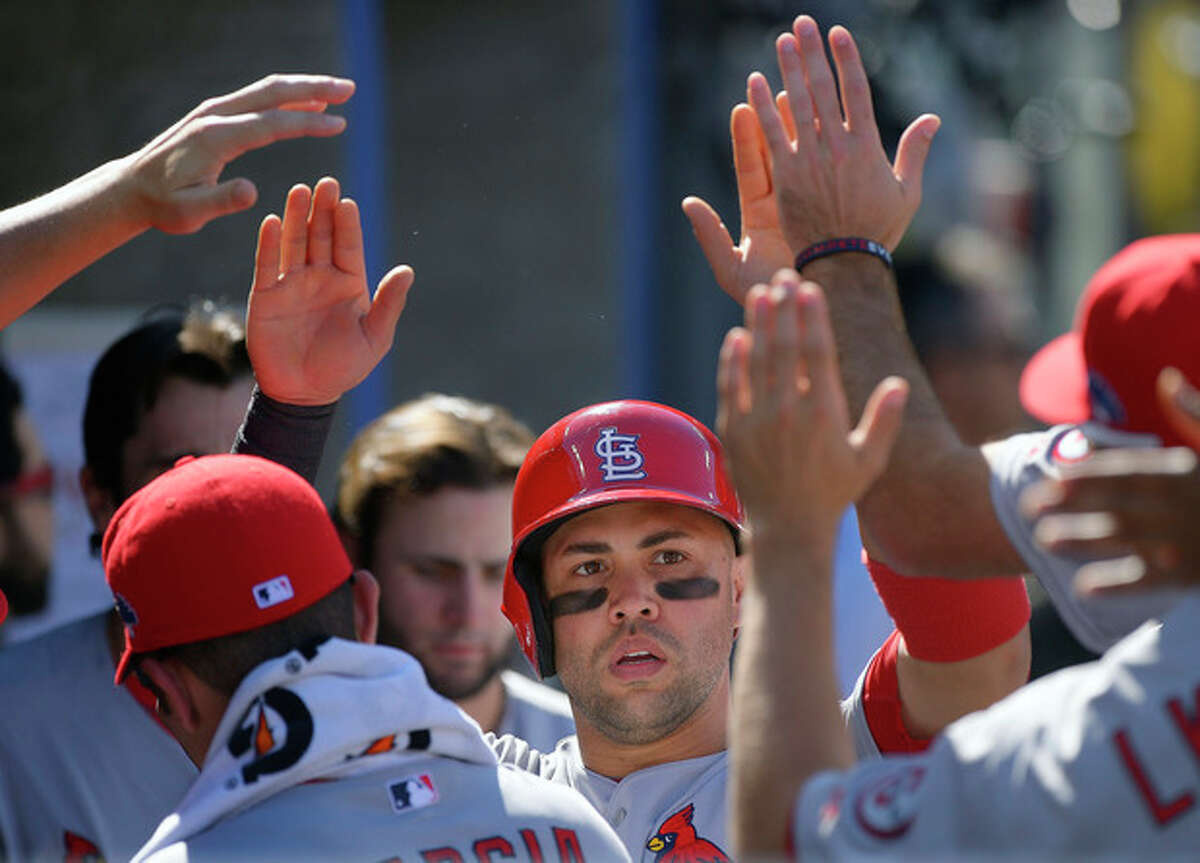 St. Louis Cardinals' Carlos Beltran, center, is congratulated after scoring during the third inning of Game 5 of the National League baseball championship series against the Los Angeles Dodgers Wednesday, Oct. 16, 2013, in Los Angeles. (AP Photo/Mark J. Terrill)