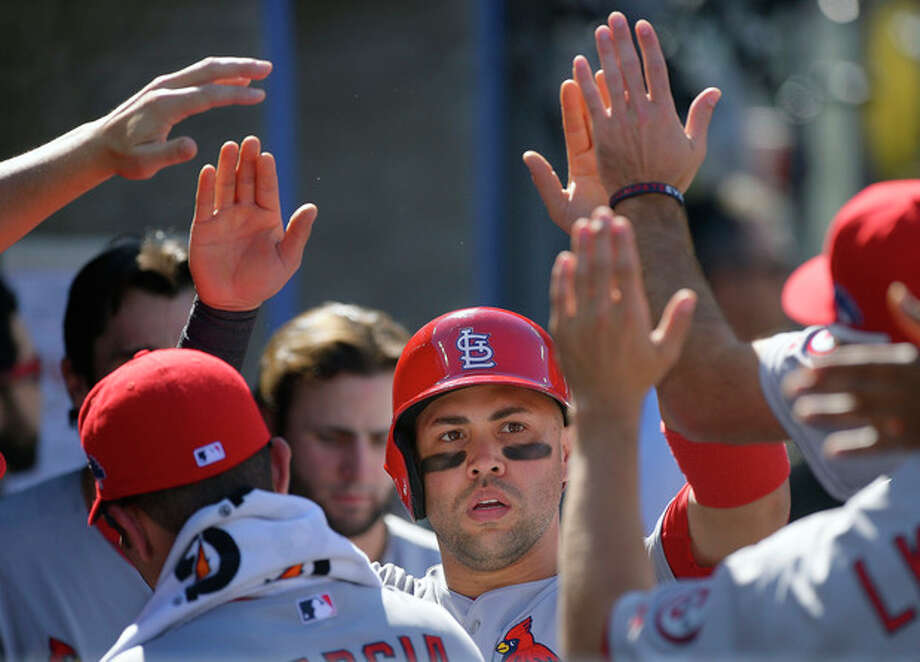 St. Louis Cardinals' Carlos Beltran, center, is congratulated after scoring during the third inning of Game 5 of the National League baseball championship series against the Los Angeles Dodgers Wednesday, Oct. 16, 2013, in Los Angeles. (AP Photo/Mark J. Terrill) / AP